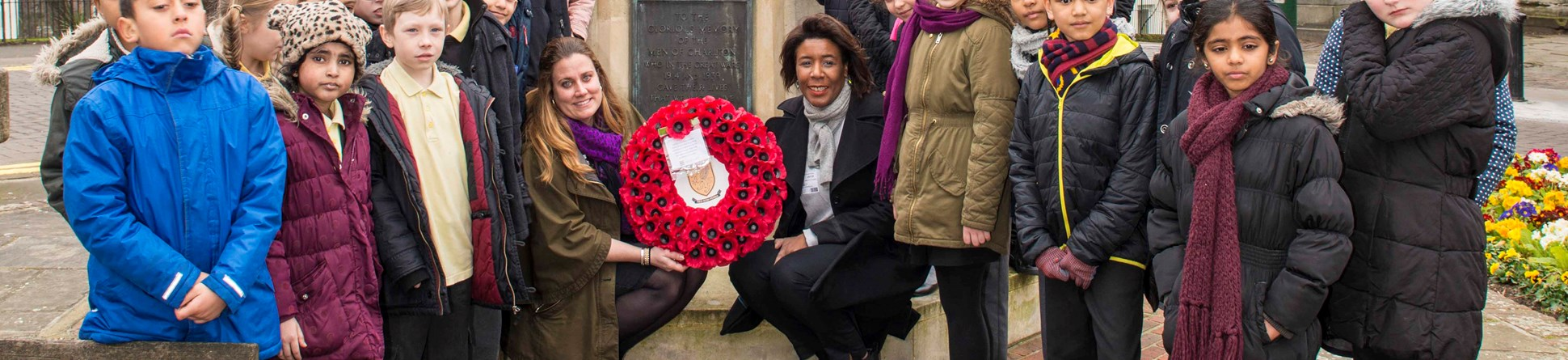 Children from Charlton Manor Primary School, Tiva Montalbano First World War Programme Manager at Historic England and Cllr Denise Scott-Mcdonald gather at the war memorial to lay a wreath.