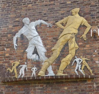 Relief of Boys Playing Football by Peter Laszlo Peri, 1951-2. Wareham House, South Lambeth Estate, Fentiman Road, London. Listed Grade II © Historic England