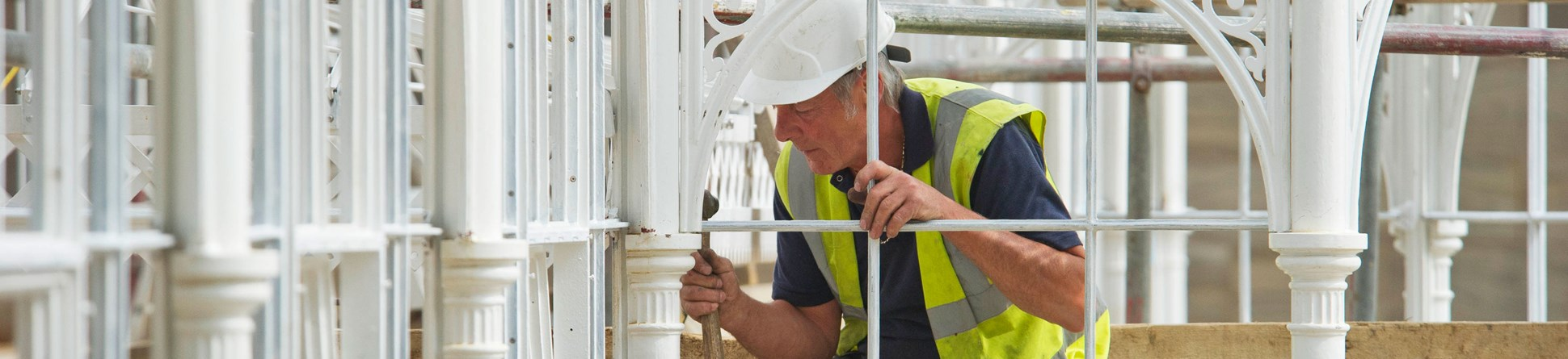 A man wearing hard hat and high vis jacket sits on scaffolding while working on ornate white ironwork of Wentworth Castle conservatory.