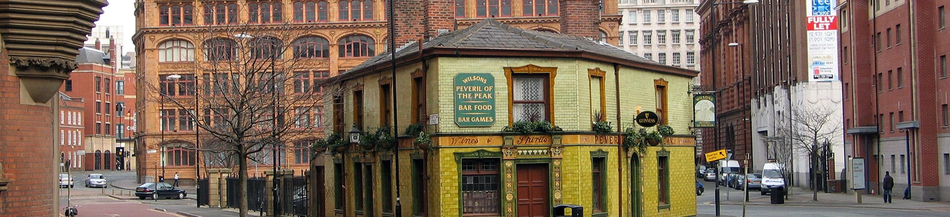 Exterior photo of the green tiled front of the Peveril of the Peak pub.
