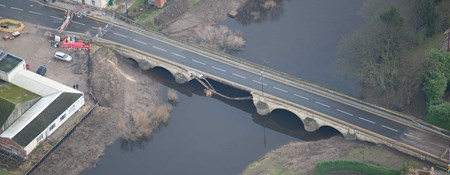 Aerial photograph of a damaged historic bridge.