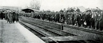 Codford station, Wiltshire. This image conveys the remarkable changes brought about at little country stations which were originally constructed to serve only a small number of passengers and which, during the war, were over-flowing with workers. The men pictured here waiting for a workmen's train were employed erecting huts for military camps on nearby Salisbury Plain. (Pratt 1921 'British Railways in the Great War')