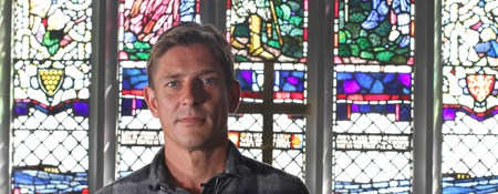 Man standing in front of stained glass windows