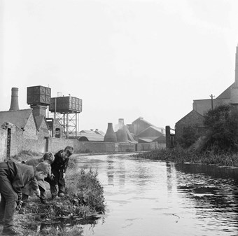 Three boys on the bank of the Caldon Canal with the kilns of Joiners Square Mill in the background